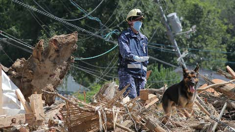 TOPSHOT - A member of Maritime Self Defense Forces searches for missing persons at a flood damage site in Kure, Hiroshima prefecture on July 12, 2018. - The toll in record rains that have devastated parts of Japan rose July 12 to 199, a top government spokesman said. Local media said search operations are continuing, with dozens of people still missing after the worst weather-related disaster in Japan in over three decades. (Photo by JIJI PRESS / JIJI PRESS / AFP) / Japan OUT        (Photo credit should read JIJI PRESS/AFP/Getty Images)