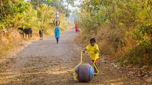 Tribal women, trudging uphill to their village with drinking water from Vanvadi open well, with an innovative rotatable water container. (Sanjiv Valson and Rishi Gangoli)