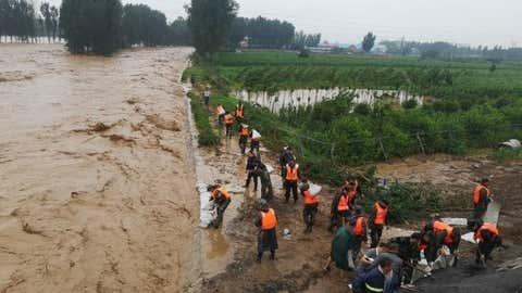 Relief workers reinforce a dam in Xiaozhuang Village in Jiaozuo, central China's Henan Province, July 22, 2021 (Photo by Wu Jianfeng/Xinhua/IANS)