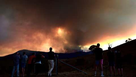 People look at a bushfire at the Namadgi National Park in Canberra, Australia on January 28, 2020. (Chu Chen/Xinhua/IANS)
