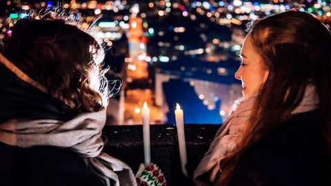 Two people look at city lights while observing Earth Hour with candles in Helsinki, Finland. (©WWF/Linda Manner)