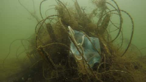 A single-use face mask underwater trapped in a ghost net. (OceanAsia)