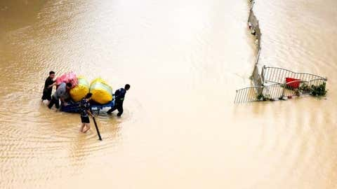 Residents transport their belongings on a flooded street in Zhengzhou, central China's Henan Province on July 21, 2021. (Xinhua/Zhu Xiang/IANS)