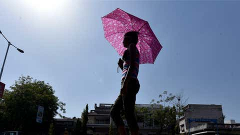 A resident of Ahmedabad, Gujarat uses an umbrella to protect herself from the scorching heat. (Yogesh Chawda/TOI, BCCL, Ahemdabad)