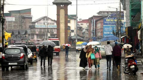 People walk through the rain in Srinagar. (Bilal Bahadur/TOI, BCCL, Delhi)