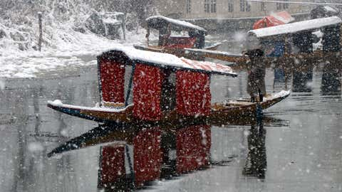 A boatman at Dal Lake during fresh snowfall in Srinagar on January 3.