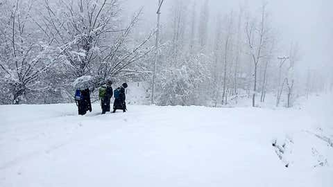 Children walk across a snow-covered road during heavy snowfall across the valley on Wednesday.