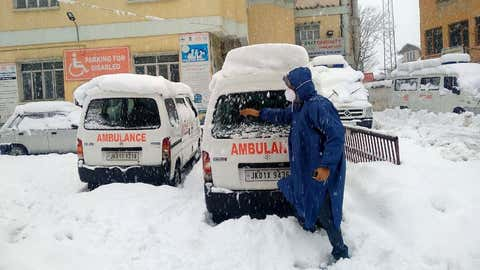 A  man clears the snow from hospital ambulance during heavy snowfall in Kashmir on January 6.