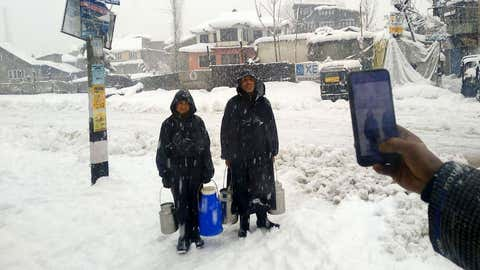Milkmen and other persons associated with essential services delivering their services in Srinagar amid heavy snowfall on Wednesday, January 6.