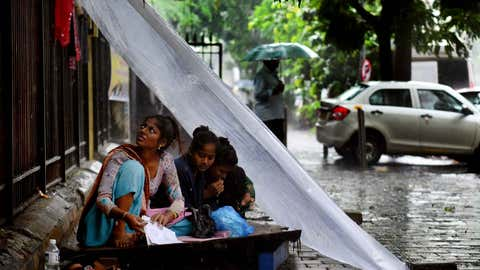 People protecting themselves from polythene sheets during rains in Mumbai. (SL Shanth Kumar/TOI, BCCL, Mumbai)