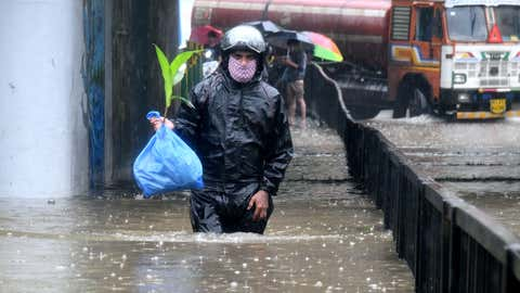 A man walks through the waterlogged street in Mumbai. (KK Choudhary/TOI, BCCL, Mumbai)