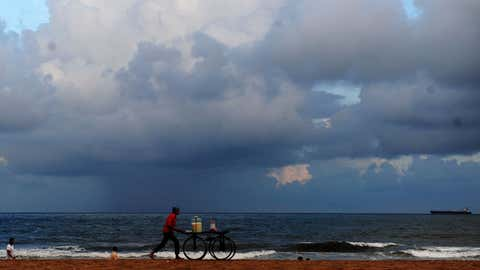 A candy seller walks at Marina Beach in Chennai, Tamil Nadu during the monsoon season. (SL Shanth Kumar/BCCL Chennai)