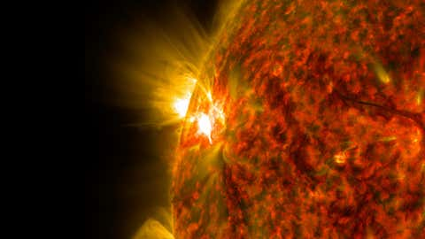File photo: The bright flash of an M-class flare is seen exploding on the left side of the sun in this image from Nov. 5, 2014. The image was captured by NASA's Solar Dynamics Observatory in extreme ultraviolet light that was colorized in red and gold.(NASA/SDO)