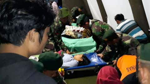 Indonesian soldiers tend to a woman injured in the earthquake at a makeshift hospital in Lombok, Indonesia, Sunday, Aug. 5, 2018. A strong earthquake struck Indonesia's popular tourist island of Lombok on Sunday, triggering a tsunami warning, one week after another quake in the same area killed more than a dozen people. (AP Photo)