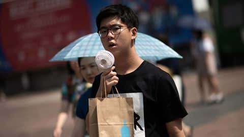 """A man cools himself with a portable fan in Tokyo on Tuesday, July 24, 2018, as Japan suffers from a heatwave. - An """"unprecedented"""" heatwave in Japan has killed at least 80 people, government officials said. , with the weather agency now classifying the record-breaking weather as a """"natural disaster. (Martin Bureau/AFP/Getty Images)"""