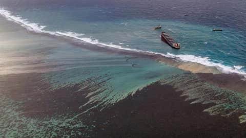 TOPSHOT - This aerial view taken on August 9, 2020 shows the site of containment operations for the leaked oil coming from the vessel MV Wakashio, belonging to a Japanese company but Panamanian-flagged, that ran aground near Blue Bay Marine Park off the coast of south-east Mauritius. - France on August 8, 2020 dispatched aircraft and technical advisers from Reunion to Mauritius after the prime minister appealed for urgent assistance to contain a worsening oil spill polluting the island nation's famed reefs, lagoons and oceans. Rough seas have hampered efforts to stop fuel leaking from the bulk carrier MV Wakashio, which ran aground two weeks ago, and is staining pristine waters in an ecologically protected marine area off the south-east coast. (Photo by - / AFP) (Photo by -/AFP via Getty Images)