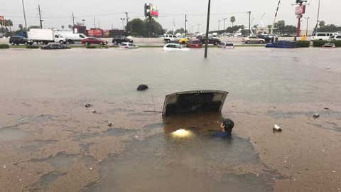 A man stays close to a car that is completely submerged underwater in McAllen, Texas. Flash flood emergencies were declared throughout Hidalgo County, Texas where several water rescues were performed for the third day in a row. (Facebook/Ricardo Desenlaze)