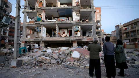 In this photo provided by the Iranian Students News Agency, ISNA, people look at destroyed buildings after an earthquake in the city of Sarpol-e-Zahab in western Iran. (Pouria Pakizeh/ISNA via AP)