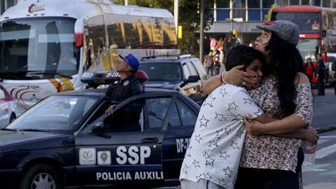 A woman embraces a boy as a powerful earthquake rocks Mexico City on February 16, 2018. A strong earthquake shook southern and central Mexico Friday, causing panic less than six months after two devastating quakes that killed hundreds of people. No buildings collapsed, according to early reports. But two towns near the epicenter, in the southern state of Oaxaca, reported damage and state authorities said they had opened emergency shelters. (YURI CORTEZ/AFP/Getty Images)