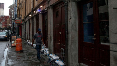 A man walks past sandbags lining a storefront in New Orleans on July 12, 2019, ahead of Hurricane Barry. The city escaped severe damage from the storm. (Seth Herald/AFP/Getty Images)