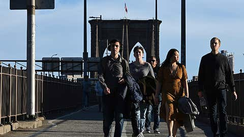 Holding their winter coats over their arms, pedestrians walk the Brooklyn Bridge during spring like temperatures nearing 70 degrees, in New York, NY, January 12, 2020. (Anthony Behar/Sipa USA)(Sipa via AP Images)