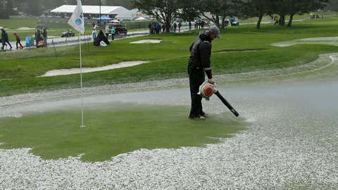 A greenskeeper uses a leaf blower to clear hail from the second green of the Pebble Beach Golf Links during the final round of the AT&T Pebble Beach Pro-Am golf tournament Sunday, February 10, 2019, in Pebble Beach, California. Play was suspended after the hailstorm. (AP Photo/Eric Risberg)