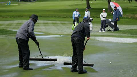 Si Woo Kim, second from right, of South Korea, stands with a rules officials and watches greenskeepers clear standing water from the second green of the Pebble Beach Golf Links during the final round of the AT&T Pebble Beach Pro-Am golf tournament Sunday, February 10, 2019, in Pebble Beach, California.