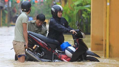 Várias pessoas empurram uma scooter numa rua inundada em Hoi An, Vietname. (AP Photo/Hau Dinh)