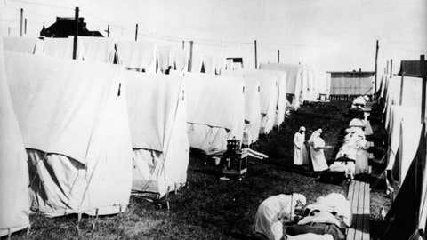 Durante a epidemia de gripe de 1918 foi necessário criar hospitais improvisados para internar os doentes, por falta de espaço nas instituições nacionais nos EUA. Nesta imagem, podem verse médicos e enfermeiras com máscaras a tratarem os doentes. (Hulton Archive/Getty Images)