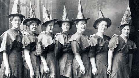 Várias mulheres vestidas bruxas, alinhadas para tirar uma foto, em 1910. (Tanscendental Graphics/Getty Images)
