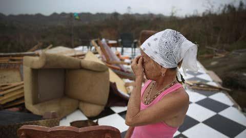 Irma Maldanado de pé ao lado daquilo que sobrou da sua casa, em Corozal, Porto Rico, que foi destruída quando passou pela região o Furacão Maria (Joe Raedle/Getty Images)