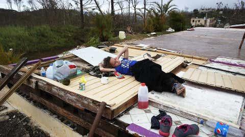Karlian Mercado, 7 anos, descansa em cima dos destroços em que se transformou a casa da sua família depois da passagem do furacão Maria.  (Joe Raedle/Getty Images)