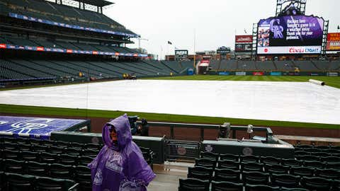 Wrapped in a poncho, a lone guard waits amid the empty seats during a weather delay to the start of a baseball game between the San Diego Padres and Colorado Rockies Tuesday, April 24, 2018, in Denver. (AP Photo/David Zalubowski)
