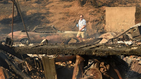 Eyad Jarjour (L) views his neighbor's burned residence after flames from the Saddleridge Fire tore through the region in Granada Hills, California on October 11, 2019. - The fire broke out late October 10 and has scorched some 4,600 acres (1,816 hectares), and forced mandatory evacuation orders for 12,700 homes. (Photo by Josh Edelson / AFP) (Photo by JOSH EDELSON/AFP via Getty Images)