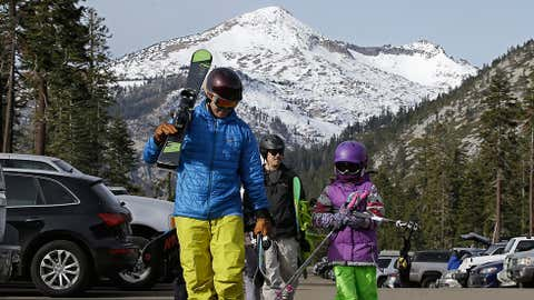 Bret McTigue, left, and his daughter Taylor, 8, head to the slopes at Sierra-at-Tahoe Ski Resort, Wednesday, Jan. 3, 2018, near Echo Summit, Calif. The California Department of Water Resources held the first snow survey of the season at the nearby Phillips Station that showed the snowpack at 1.3 inches of depth with a water content of .4 inches. California's water managers are saying it's too early yet for fears that the state is sliding back into its historic five-year drought. (AP Photo/Rich Pedroncelli)