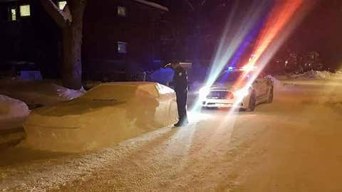 A Montreal police officer stands next to artist Simon Laprise's snow car, ticket book in hand. (Simon Laprise/L.S.D. Designs)