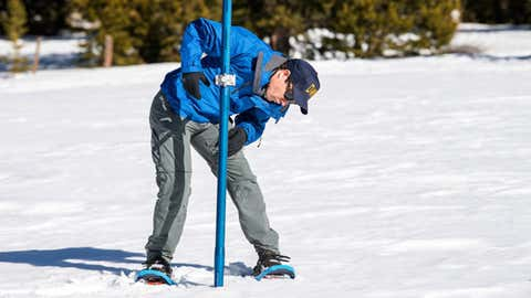 John King, a water resource engineer with the California Department of Water Resources, Snow Survey Section inserts a long aluminum snow depth survey pole into the snow for the first DWR snow survey of the 2019 season at Phillips Station in the Sierra Nevada Mountains on Thursday, January 3, 2019.  (Ken James / California Department of Water Resources)
