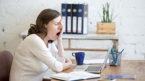 Portrait of young woman sitting at table in front of laptop, sleepy, tired, overworked, lazy to work. Attractive business woman yawning in home office relaxing or bored after work on laptop computer