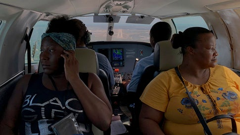 """Dimple Lightbourne, left, and her mother Carla Ferguson sit in a plane as it prepares to land in Nassau, Bahamas, after they were evacuated from Abaco Island on Monday, September 9, 2019. """"I don't want to see the Bahamas for a while. It's stressful. I want to go to America,"""" said Lightbourne, a 30-year-old resident of Treasure Cay. (AP Photo/Fernando Llano)"""
