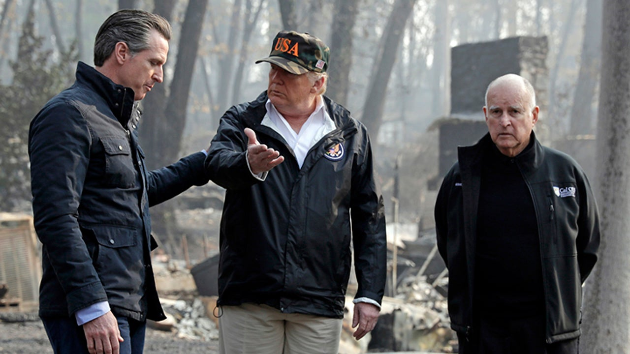 President Donald Trump talks with then-Gov.-elect Gavin Newsom, left, as California Gov. Jerry Brown listens during a visit on November 17, 2018, to a neighborhood impacted by the Camp wildfire in Paradise, California.  (AP Photo/Evan Vucci)