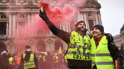 """Protesters gather at Place de l' Opera on December 15, 2018, during a """"yellow vest"""" protest in Paris, France. The protesters gathered in Paris for a fifth weekend despite President Emmanuel Macron's recent attempts at policy concessions, such as a rise in the minimum wage and cancellation of new fuel taxes."""