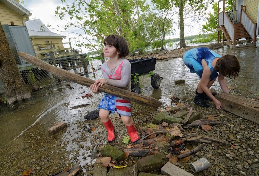 Delilah Campbell, 4, left, and her sister, Tallulah Campbell, 8, clear out driftwood and other debris in preparation of Tropical Storm Barry near New Orleans on Thursday, July 11, 2019.