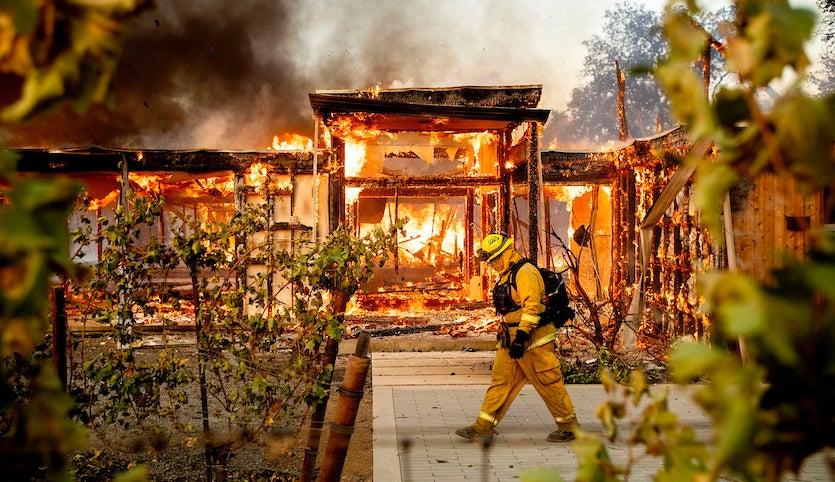 Woodbridge firefighter Joe Zurilgen passes a burning home as the Kincade Fire rages in Healdsburg, Calif., on Sunday, Oct 27, 2019