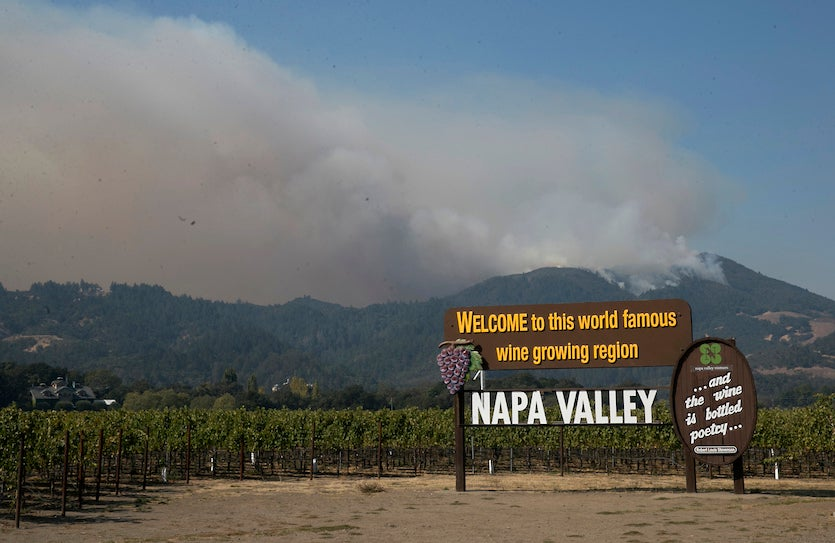 Smoke billows from a fire burning in the mountains over Napa Valley, Friday, Oct. 13, 2017, in Oakville, Calif.