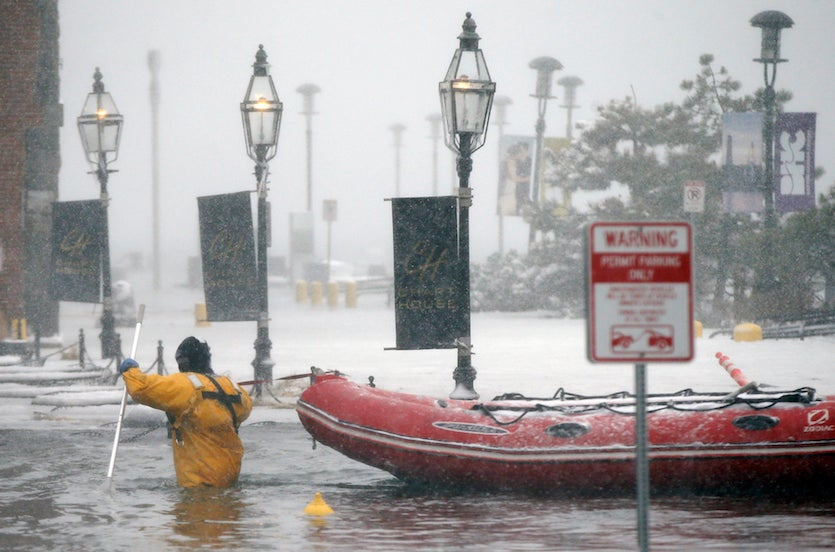 .  A Boston firefighter wades through flood waters from Boston Harbor on Long Wharf on Thursday, Jan. 4, 2018