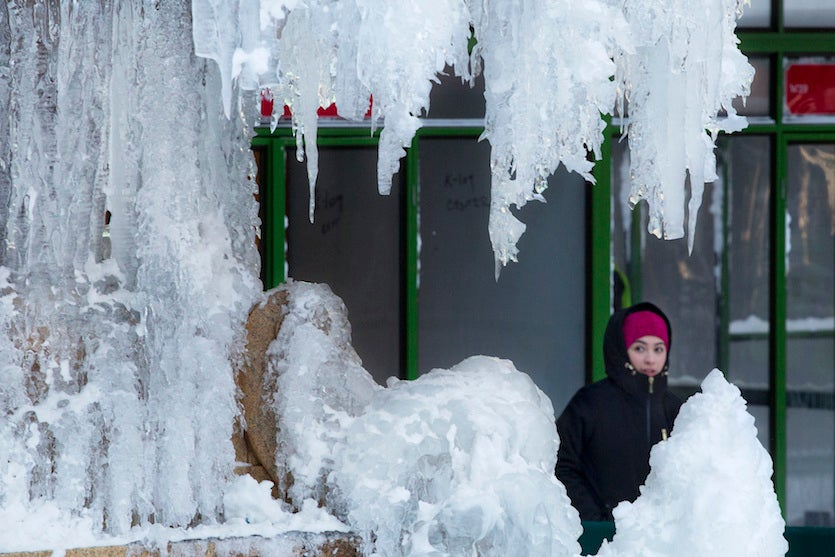 A woman passes an ice-covered fountain in New York's Bryant Park, Friday, Jan. 5, 2018