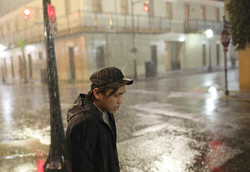 Charles Phanthapannha stands in the rain outside a bar as Tropical Storm Gordon approaches on Tuesday, Sept. 4, 2018 in Mobile, AL