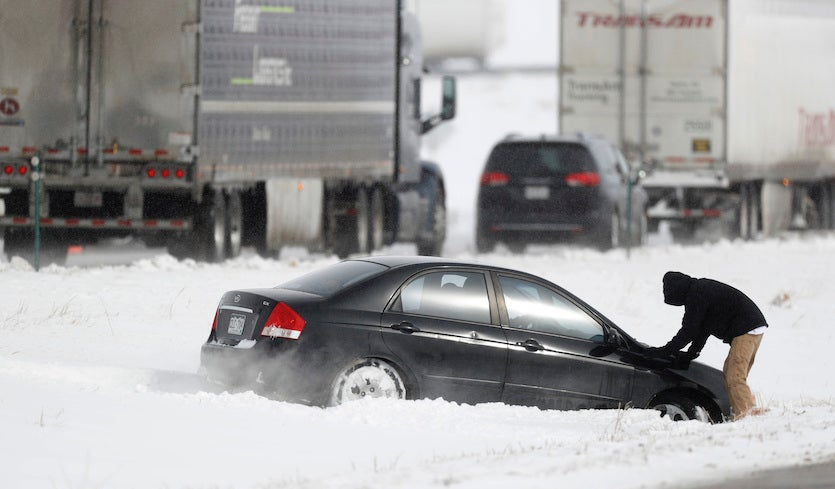 A motorist struggles to free his sedan after sliding off Interstate 70 in Aurora, Colorado, just east of Denver, on Tuesday, October 29, 2019