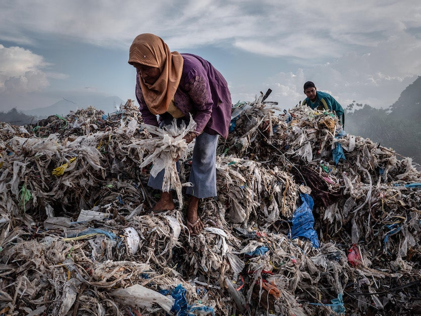 A woman collecting plastic to recycle at a import plastic waste dump on December 4, 2018 in Mojokerto, East Java, Indonesia