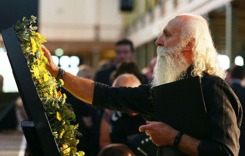 Attendees pay their respects by laying flowers during the state commemoration for the 10-year anniversary of the 2009 Victorian bushfires on 2/4/19 in Melbourne